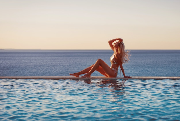 プールで海での休暇の概念。海とパノラマのプールの端にある豪華な水着の女の子