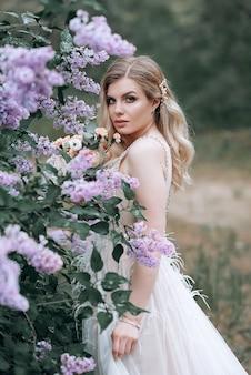 Молодая красивая невеста со свадебным букетом возле кустов сирени