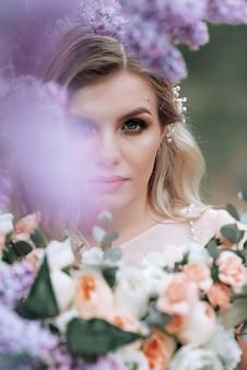 ライラックの茂みの近くのウェディングブーケを持つ若い美しい花嫁