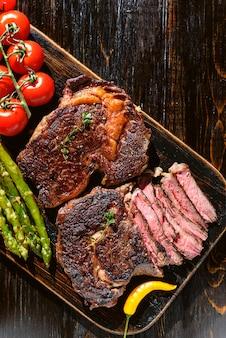 Ужин для двух сочных вкусных стейков, спаржи с пармезаном и овощами.