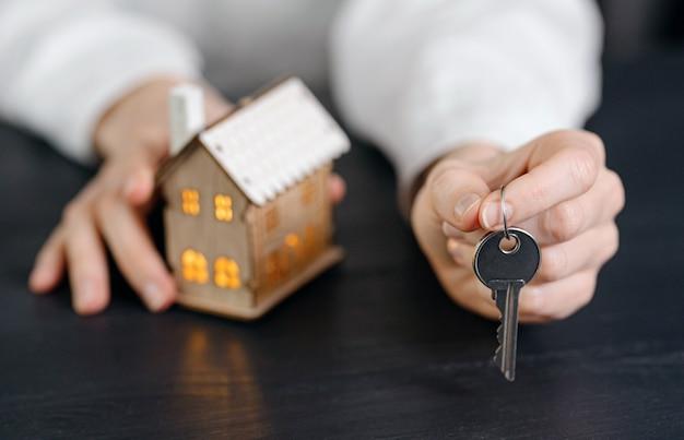 女性の手にある家の鍵と、近くに明るい窓がある家の小さなモデル。あなたの家を取得する概念