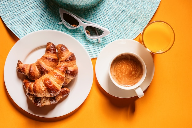 帽子、サングラスクロワッサン、コーヒーのカップと太陽の下で黄色のテーブルの上のオレンジジュースのガラス