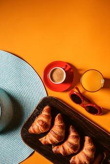 Шляпа, солнцезащитные очки, круассан с чашкой кофе и стакан апельсинового сока на желтом столе на солнце