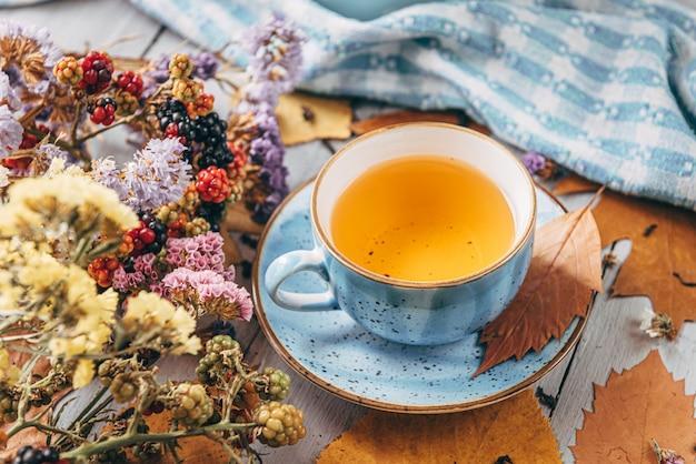 Осенний согревающий чай на деревянном столе с осенними листьями деревьев, лежащими рядом