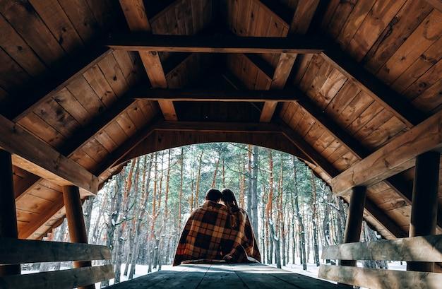 愛する若いカップルが雪に覆われた森の山で休んでいます。ジョイントレストのコンセプト