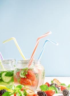 チューブ付きガラス瓶に入れた新鮮な果物と野菜のデトックススムージー