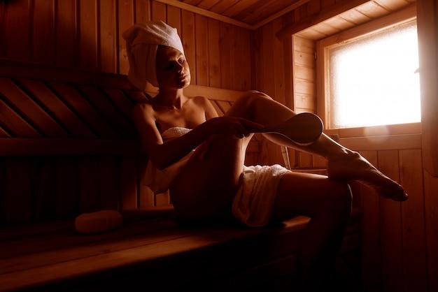 Девушка в санаторно-курортном лечении в традиционной сауне с кисточкой для кожи и мочалкой