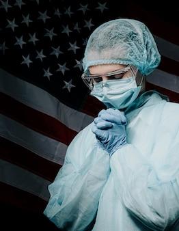 忙しい一日の後に疲れた医師、アメリカの国旗を背景に祈る医師