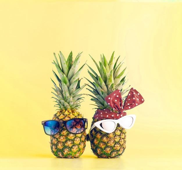 バカンスリゾートでのショッピングの愛のカップル。男と明るい背景の女の子の形のメガネとパイナップル