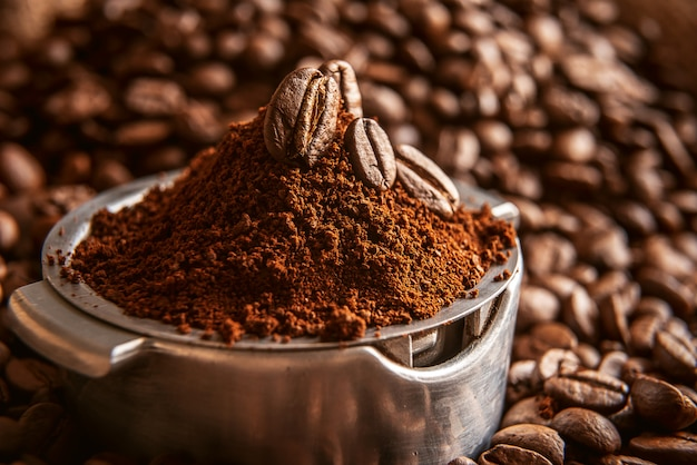 Молотый кофе наливают в держатель, на котором лежат зерна жареного, ароматного кофе. на фоне жареных зерен