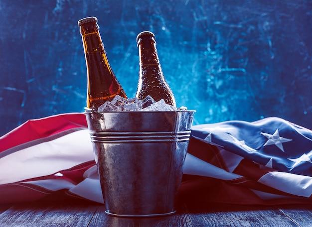 Две бутылки пива в ведерке со льдом с американским флагом, лежащим поблизости. концепция празднования дня независимости