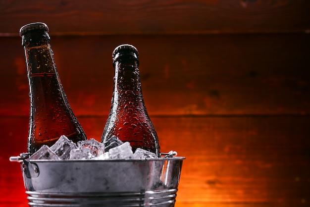 Две бутылки пива в ведерке со льдом