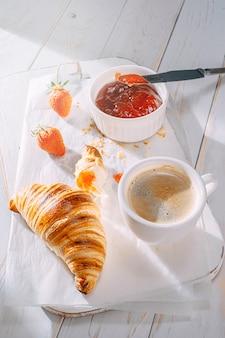 朝の太陽の下でジャムとコーヒーをテーブルの上で焼きたての焼きたてのクロワッサン。おいしい朝食のコンセプト
