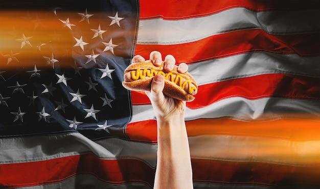 Классический американский хот-дог в руке на фоне американского флага