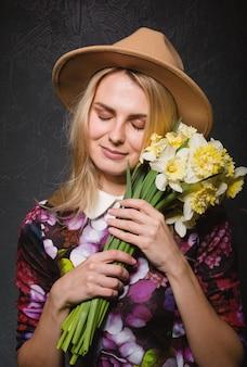 手に水仙の花束とドレスを着た女性