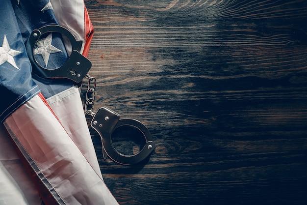 アメリカの国旗と木製のテーブルに手錠