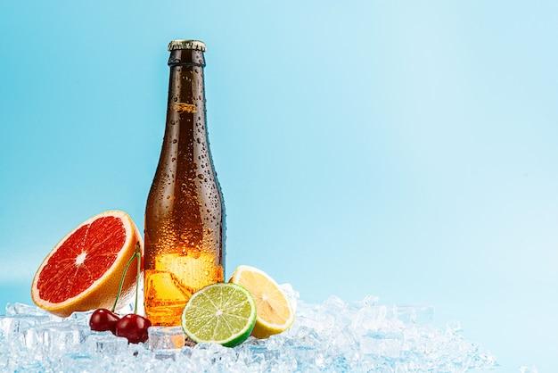 氷の上の茶色のガラスビールの閉じたボトル。果物は近くにあります。フルーツクラフトビールまたはサイダーの概念
