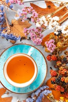 木製の表面に果実と紅葉とホットリーフティーとマグカップの静物