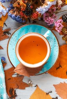 Композиция натюрморт с кружкой горячего листового чая с ягодами и осенними листьями на деревянной поверхности