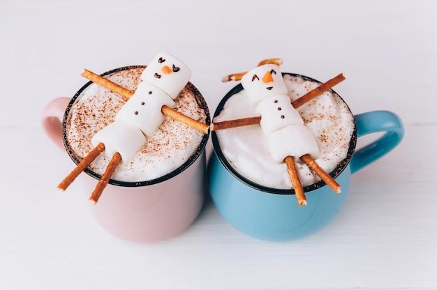 Кружки с горячим шоколадом, в которых отдыхают мужчины из зефира. концепция пары