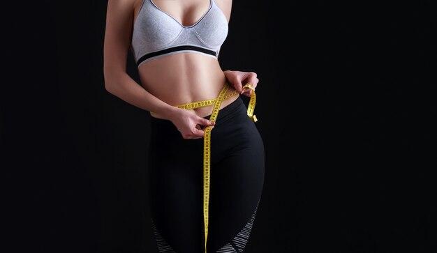 Девушка с идеальной спортивной фигурой измеряет размер своей талии