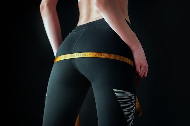 完璧なスポーツ図を持つ少女は、お尻のサイズを測定します