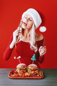 Девушка в красном платье и шляпу санта с гамбургером в руках