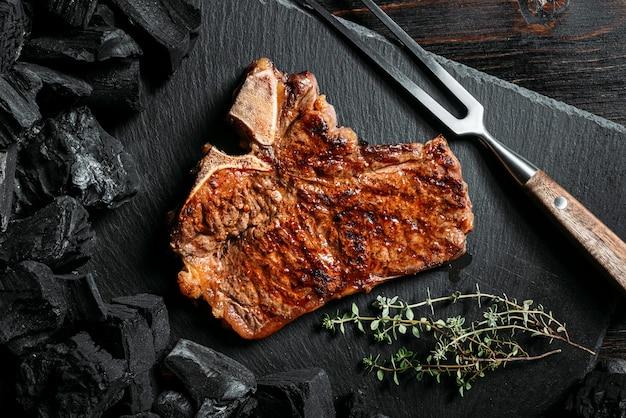 Стейк для барбекю на черной грифельной доске с мясной вилкой и углями гриля