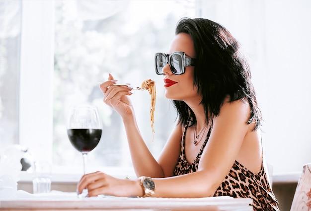 彼女の赤ワインを洗い流すレストランでパスタを食べる少女