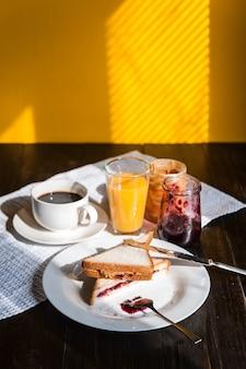 朝の太陽の下で木製のテーブルにコーヒーとピーナッツバターとジャムの朝食