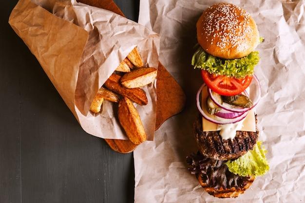ハンバーガーは、木製のテーブルのクラフト紙で成分に分解されました。チップのパッケージ。