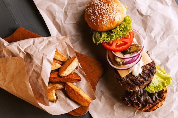 Бургер разложен на составные части на крафт-бумаге на деревянном столе. пакет чипсов.