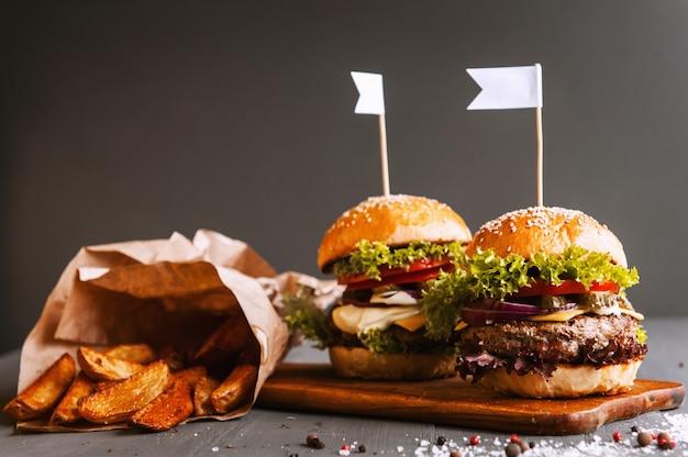 Два аппетитных, вкусные домашние бургеры рубить говядину. на деревянном столе .. маленькие белые флаги вставлены в гамбургеры.