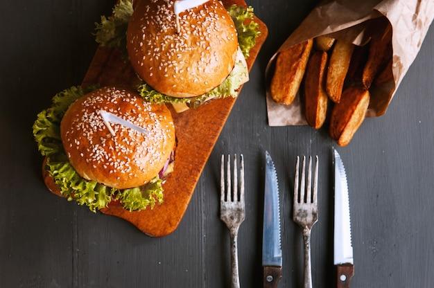 Два аппетитных, вкусные домашние бургеры рубить говядину. на деревянном столе.