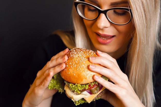 美しい若い、健康な女性は、ビーフカツレツとおいしい大きなハンバーガーを保持しています。栄養食品のコンセプト。