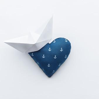 Сердце из синей ткани с принтом якорей. с бумажным корабликом на краю сердца. концепция любви к морю