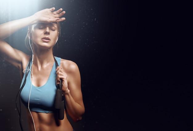 Девушка отдыхает после упражнений в тренажерном зале