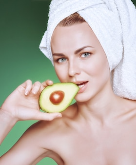 彼女の顔に栄養価の高い緑のマスクとテキスト用のスペースと緑の背景に彼女の手でアボカドと彼女の頭に白いタオルを持つ少女