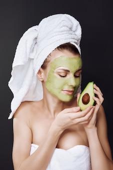 アボカドの化粧品のマスクを持つ少女。暗い背景、スタジオライト。