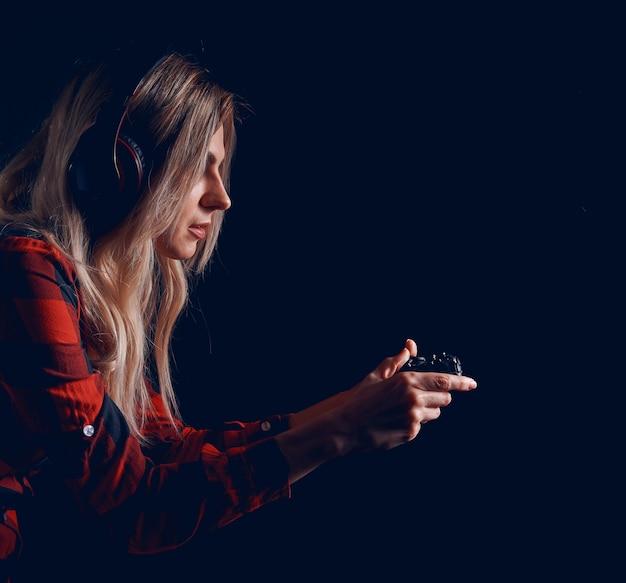 Девушка-геймер в наушниках и с джойстиком увлеченно играет на консоли
