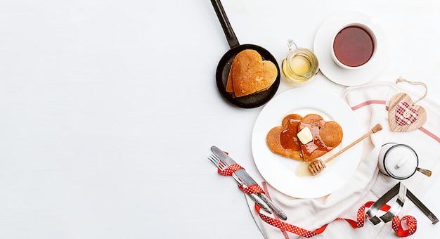 Блинчики в форме сердца на светлом фоне. концепция праздничного завтрака на день святого валентина или приятный сюрприз для любимого человека