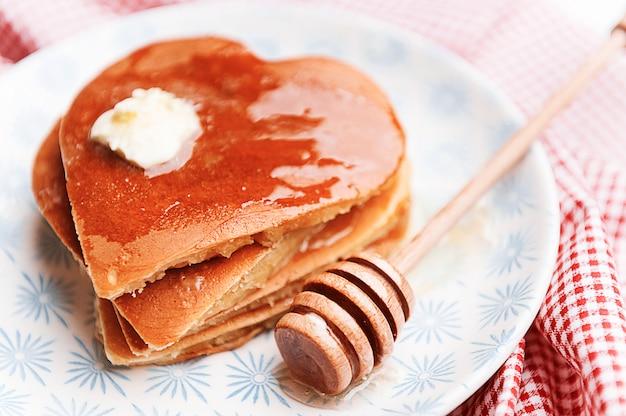 ハート形の明るい背景にパンケーキ。バレンタインデーのお祝いの朝食のコンセプト、または愛する人への楽しいサプライズ