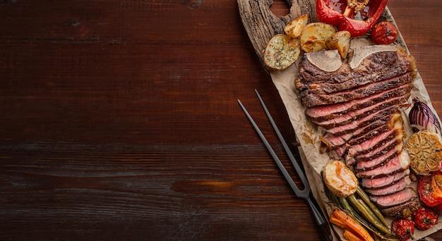 Стейк из мраморной говядины на косточке, приготовленный до состояния среднего редкого гриля. рядом со стейком овощи гриль, служащие гарниром. прекрасный праздничный ужин на двоих