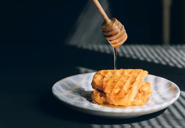 朝の太陽の光の中で、木製のテーブルの上に蜂蜜とウェーハ。
