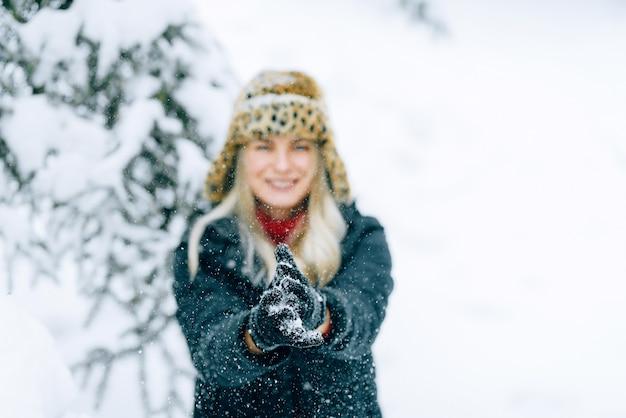 ヒョウ柄のファッショナブルな冬の帽子の少女は雪の中で喜ぶ