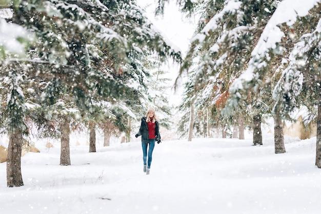 Девушка в модной зимней шапке с леопардовым принтом радуется на снегу