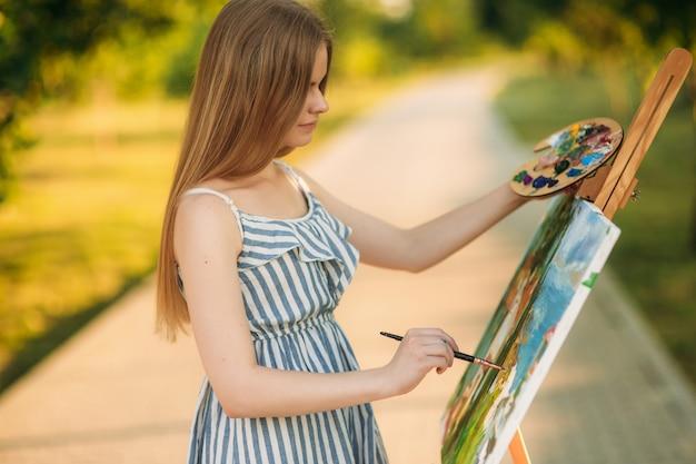 Красивая девушка рисует картину в парке с помощью палитры с красками и шпателем. мольберт и холст с рисунком.