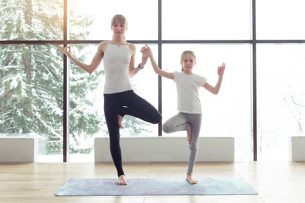 Дочь матери и ребенка в спортзале делает позу йоги