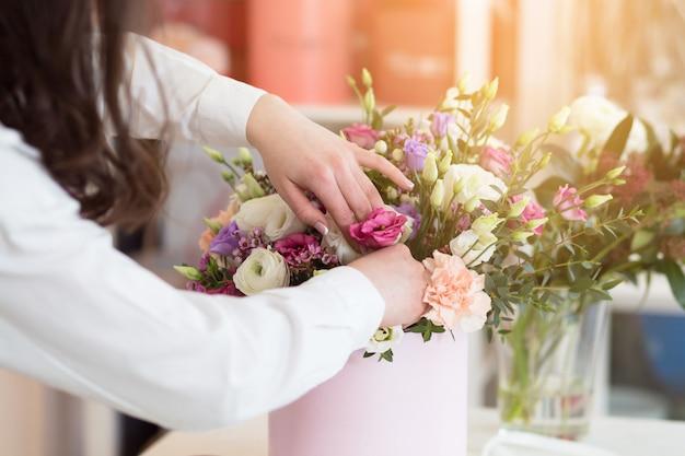 Флорист женщины делая композицию цветка в цветочном магазине