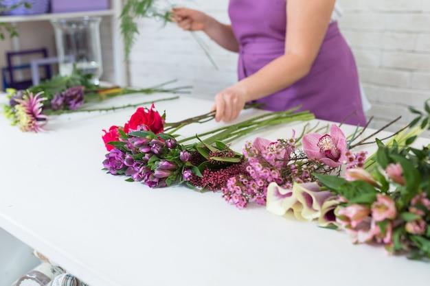 Разные цветы на белом столе в цветочном магазине